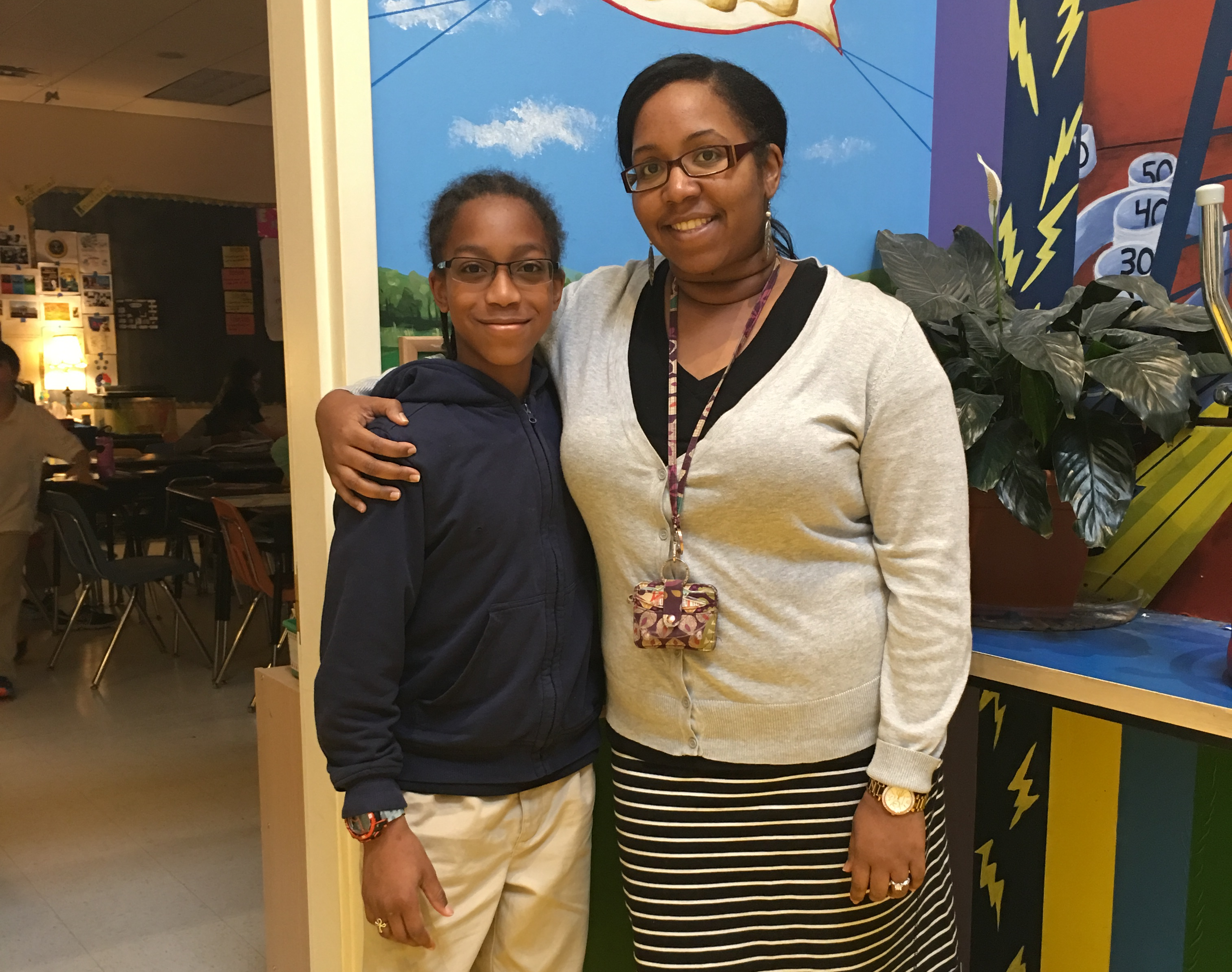 Maxwell standing next to his fifth grade teacher Ms. Tanya
