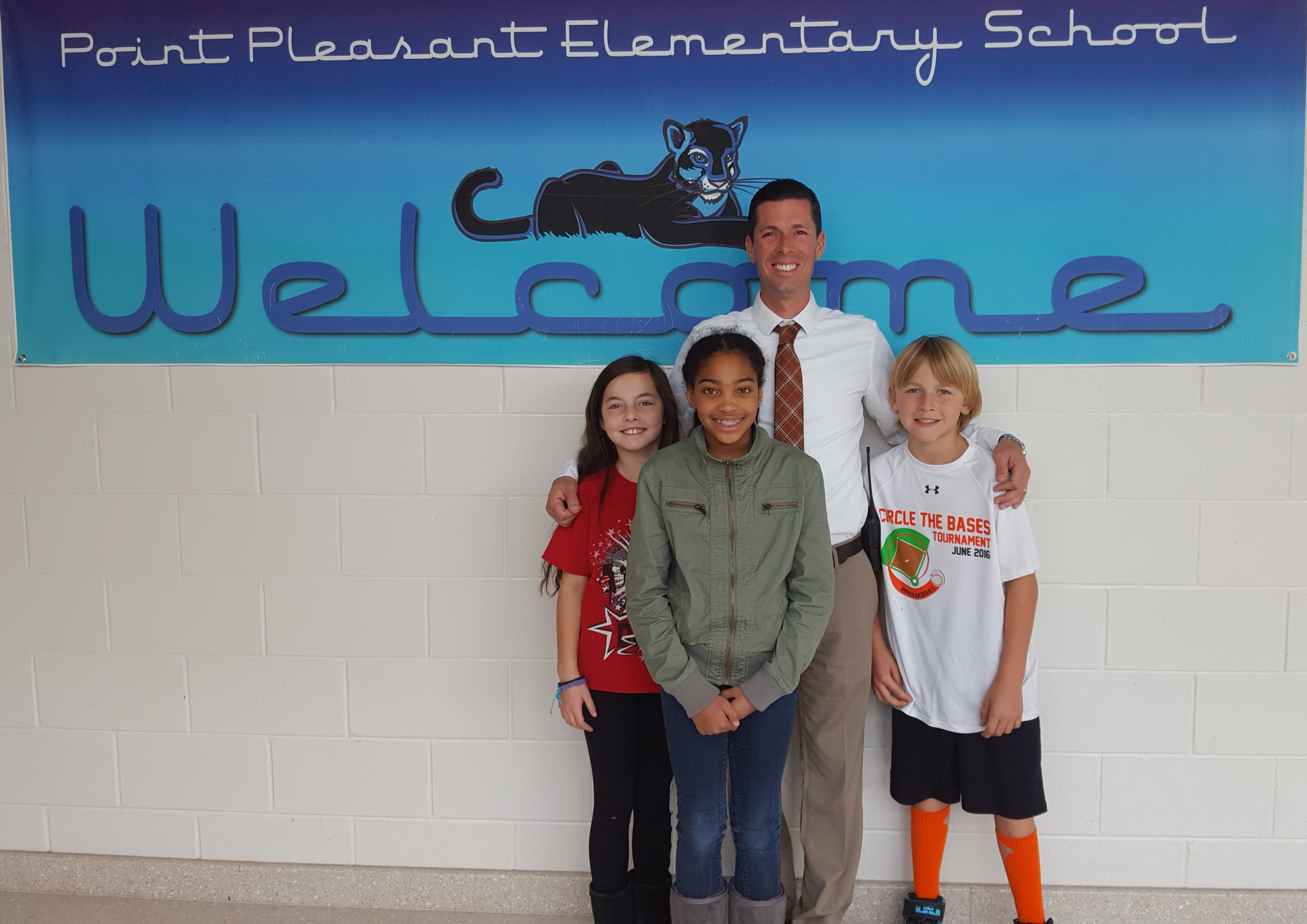 Principal Christopher Gordon standing with three students
