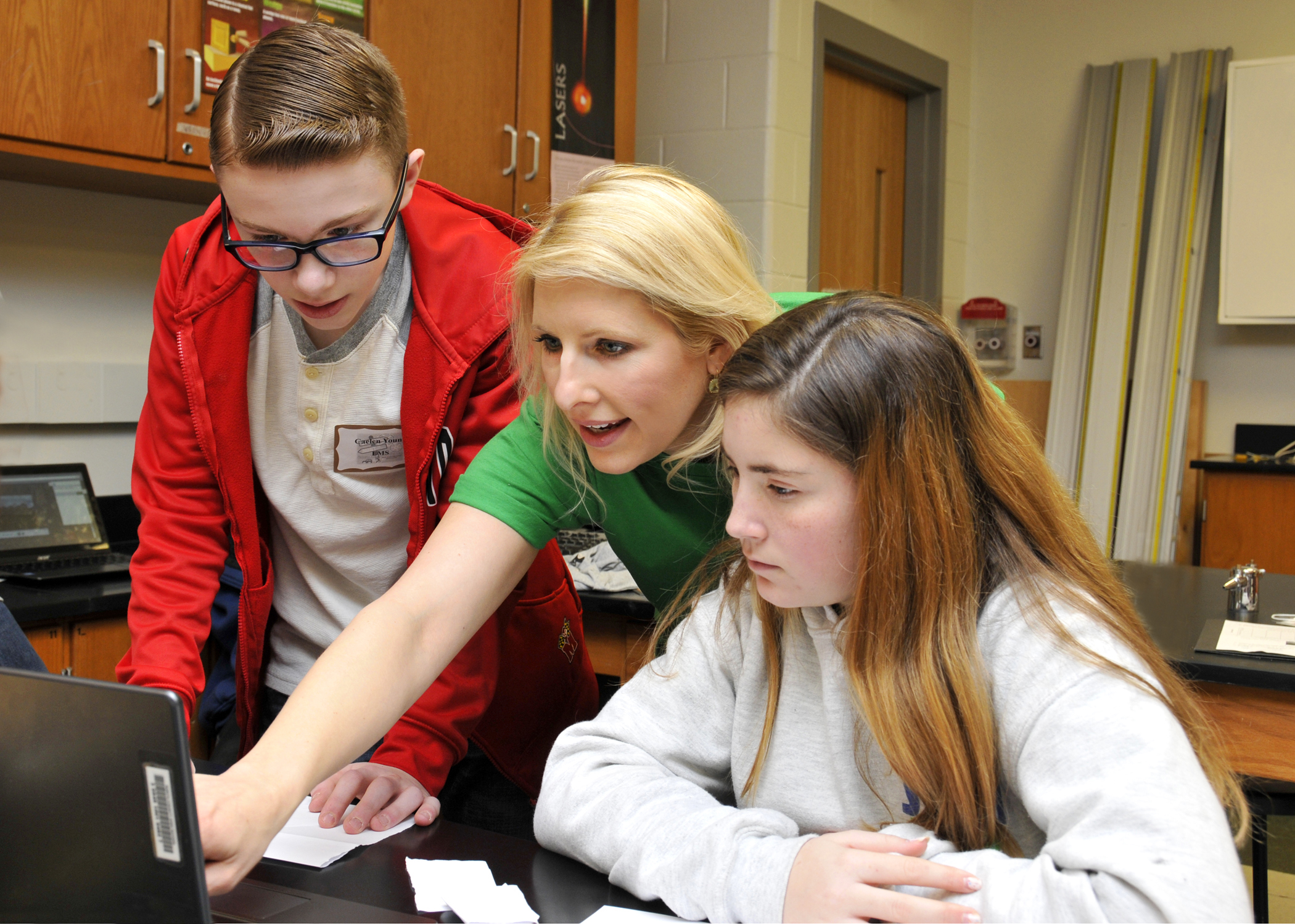 Katrina Griffin standing between two students pointing to a computer.