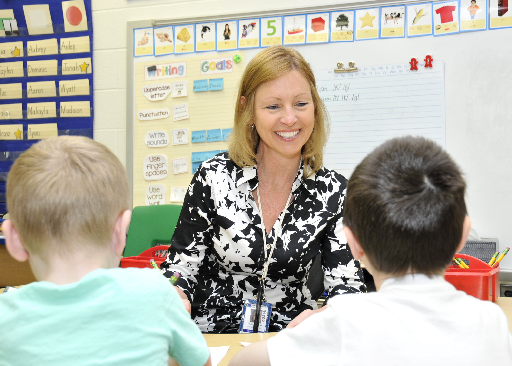 Sharon Mattoon sitting in front of two kindergarten students