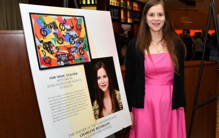 Charlene Beyerlein standing next to a poster of artwork created by her students.