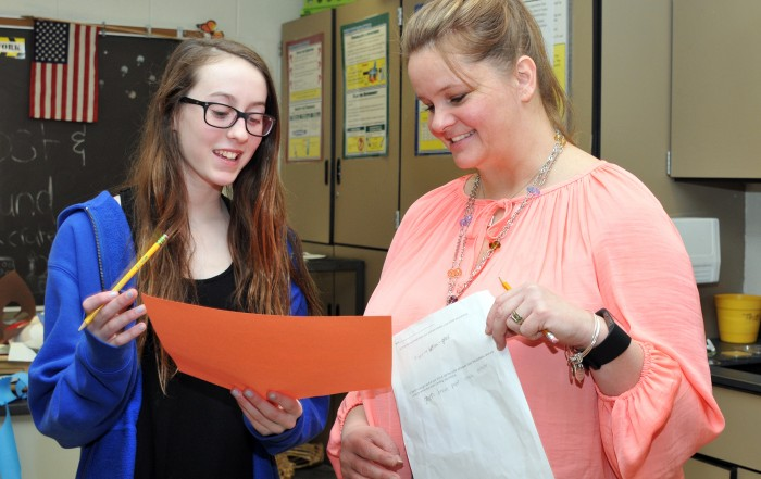 Kathleen Soares looks at some papers with a female middle school student.