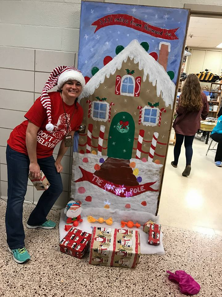 Marlene Kramer standing in front of her classroom door decorated for the holidays